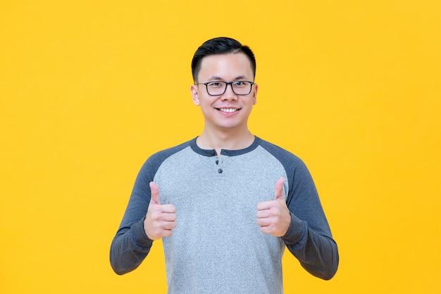 Optimistischer asiatischer mann im zufälligen t-shirt lächelnd, daumen aufgebend