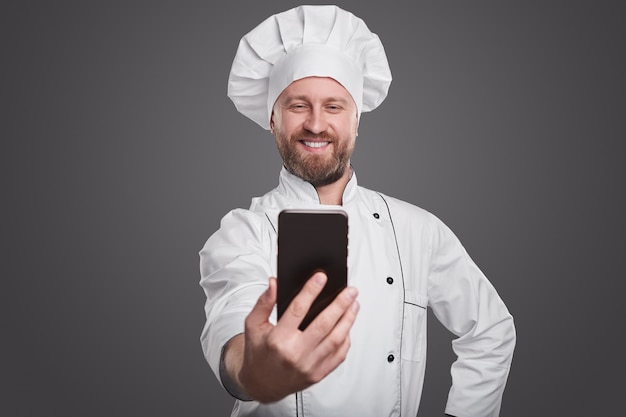 Optimistischer erwachsener bärtiger professioneller koch in der weißen kochuniform, die selfie auf handy gegen grauen hintergrund nimmt
