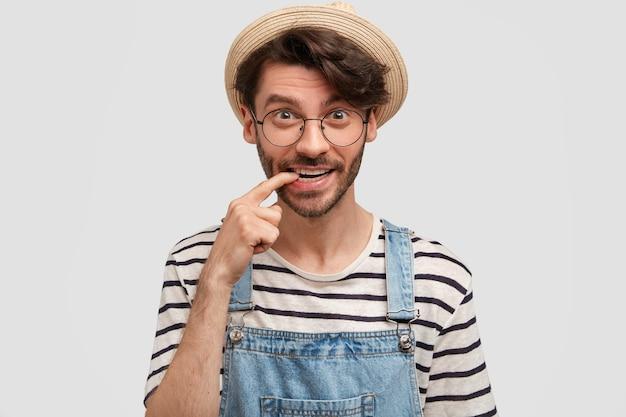 Optimistischer fröhlicher bärtiger männlicher bauer beißt zeigefinger