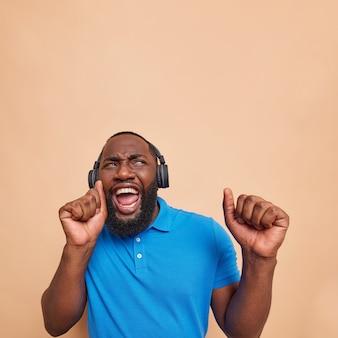 Optimistischer fröhlicher dunkelhäutiger mann tanzt unbeschwert und fängt jedes bisschen musik ein