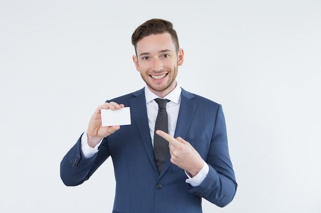 Optimistischer männlicher manager, der auf visitenkarte zeigt