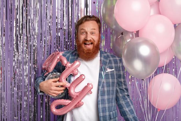 Optimistischer rothaariger mann mit dickem bart und stilvoller frisur, hält luftballons und disco-kugel, hat spree mit gästen, trägt stilvolles outfit, isoliert über lila wand. geburtstagsfeier kommt