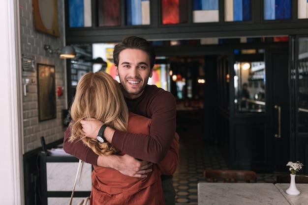 Optimistisches hübsches paar, das umarmt und mann in die kamera schaut