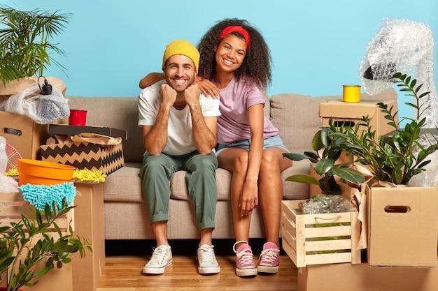 Optimistisches junges paar sitzt auf der couch, umgeben von kisten