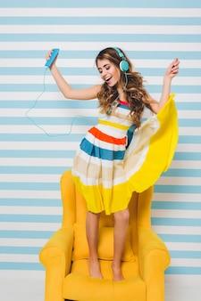 Optimistisches mädchen, das buntes kleid trägt, das im gelben sessel kühlt und entspannende musik hört und mit lächeln tanzt, das musik genießt.