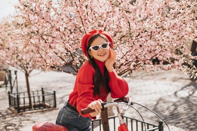 Optimistisches mädchen im roten pullover und in den gläsern, die auf fahrrad gegen hintergrund der sakura lehnen. charmante frau in der stilvollen baskenmütze, die im garten lächelt