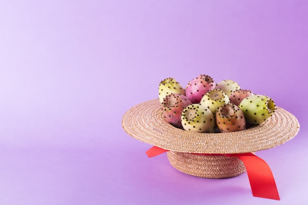 Opuntiefrucht in einem strohhut auf einem modischen purpurroten hintergrund