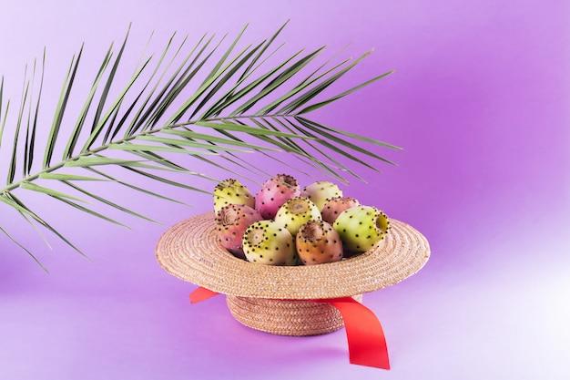 Opuntiefrucht in einem strohhut mit einem palmblatt auf einem modischen purpurroten hintergrund