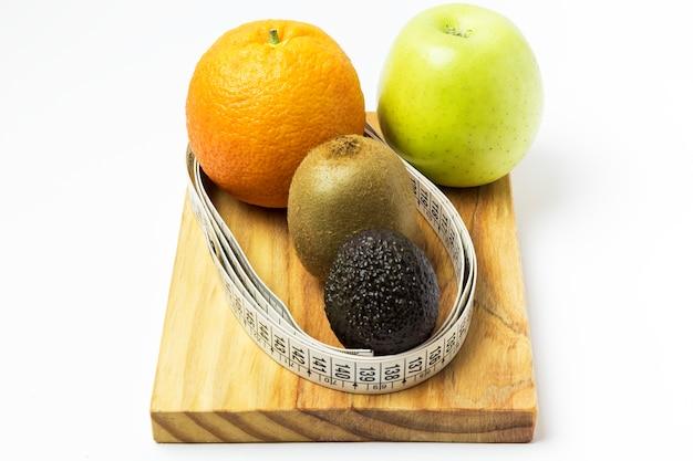 Orange, apfel, kiwi und avocado umgeben von einem maßband
