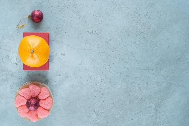 Orange auf einem roten kasten neben einer kleinen platte mit marmeladen um eine dekorative kugel auf marmor.