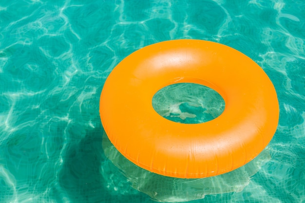 Orange aufblasbarer donut auf blauem wasser in einem swimmingpool