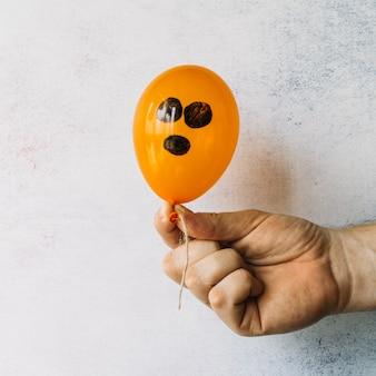 Orange Ballon mit schwarzem gemaltem Gesicht
