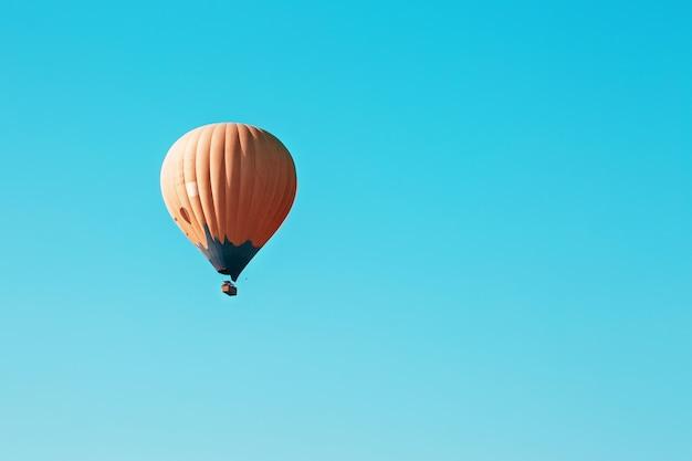 Orange ballon steigt gegen den blauen himmel an