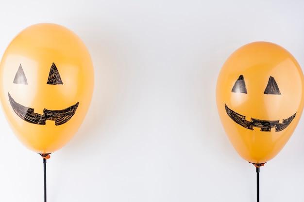 Orange ballons als kürbisse gemalt