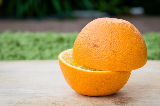 Orange beschaffenheit des halben schnittes auf holztisch.