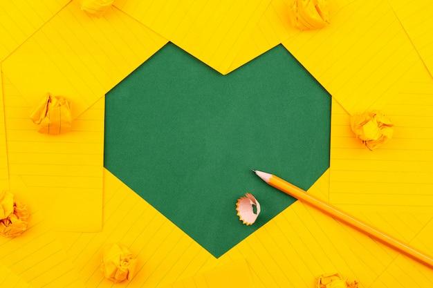 Orange blätter aus papier, bleistift und zerknitterten papieren liegen auf einer grünen schulbehörde und bilden eine rahmenherzform.