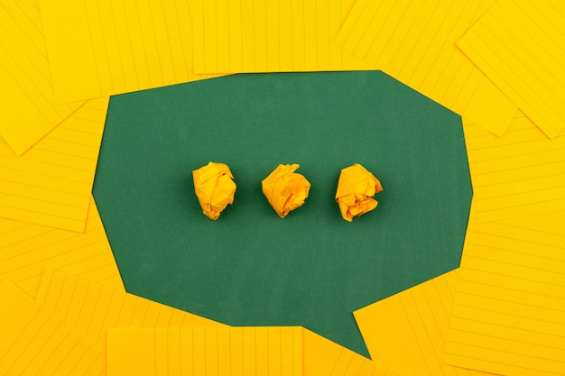 Orange blätter liegen auf einer grünen schulbehörde und bilden eine sprechblase mit drei zerknitterten papieren