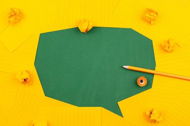 Orange blätter papier liegen auf einer grünen schulbehörde und bilden eine sprechblase mit bleistift, zerknitterten papieren und textfreiraum.