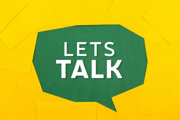 Orange blätter papier liegen auf einer grünen schulbehörde und bilden eine sprechblase mit text, lassen sie uns reden