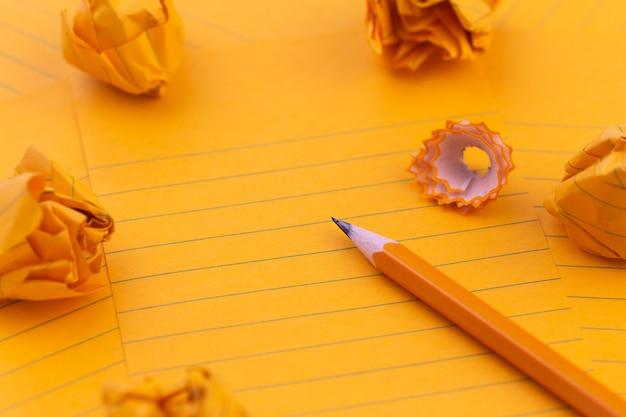 Orange blatt papier, bleistift, briefpapier und leerer platz für ihren text.