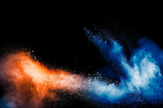 Orange blaue farbpulverexplosion auf schwarzem hintergrund.