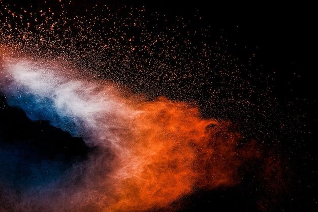 Orange blaue pulverexplosion auf schwarzem hintergrund. orange blaue farbe staubspritzerwolken.