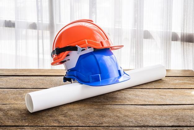 Orange, blauer harter schutzhelmbauhut für sicherheitsprojekt des arbeiters als ingenieur oder arbeitskraft