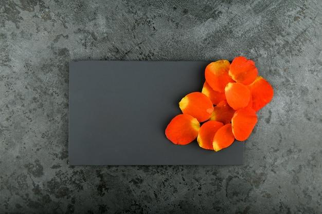 Orange blütenblätter auf einem schwarzen. platz für eine inschrift. blütenblätter auf marmor.