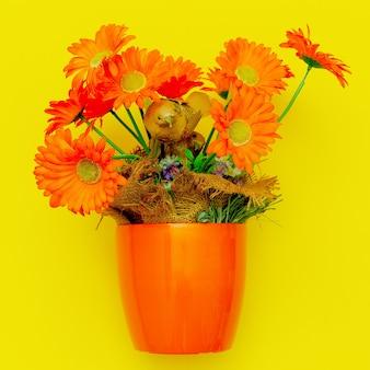 Orange blumen in einem topf auf gelbem grund. jahrgang. flache lay-kunst