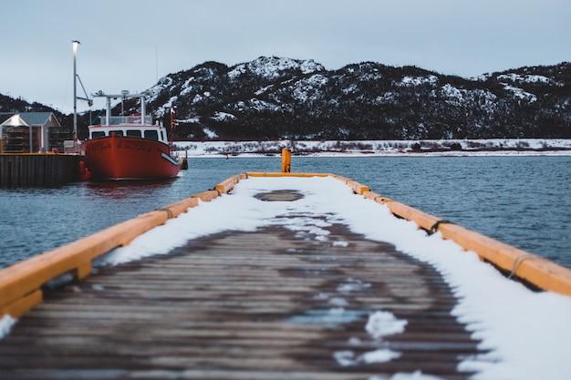 Orange boot auf dem gewässer, das berg betrachtet