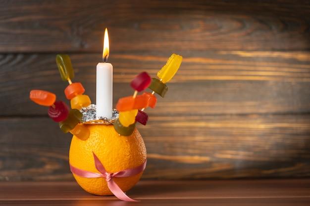 Orange christingle ist ein symbolisches objekt, das in den advents-, weihnachts- und offenbarungsgottesdiensten vieler christlicher konfessionen verwendet wird