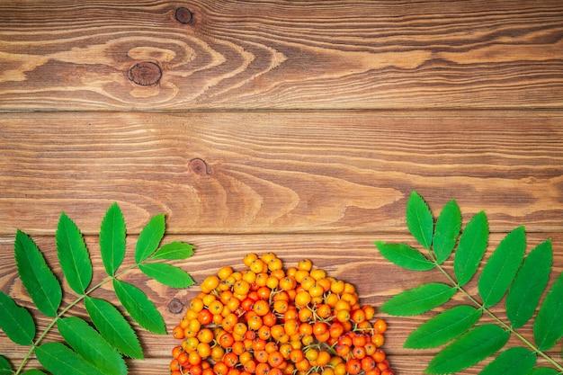 Orange ebereschenbeeren und grüne blätter auf braunen weinlesebrettern