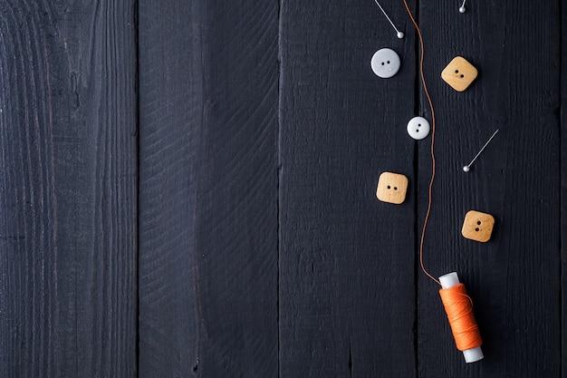 Orange fadenspule, stifte und knöpfe zum nähen auf einem hölzernen schwarzen hintergrund. speicherplatz kopieren