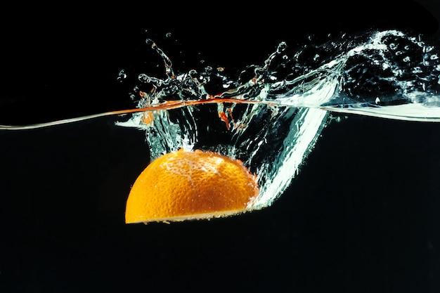Orange fällt ins wasser und macht spritzer