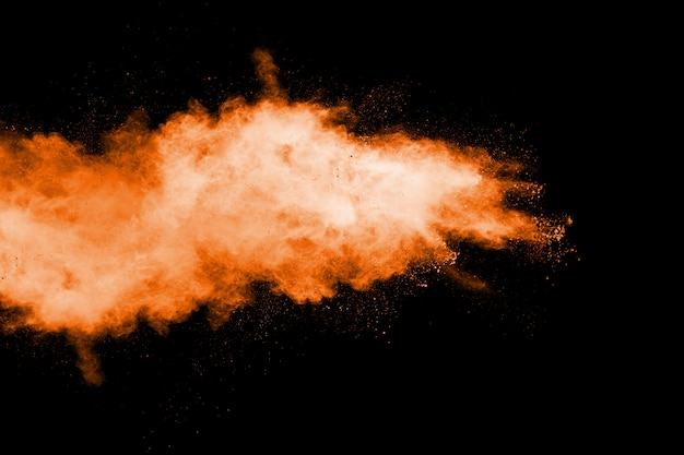 Orange farbpulver-explosion auf schwarzem hintergrund.