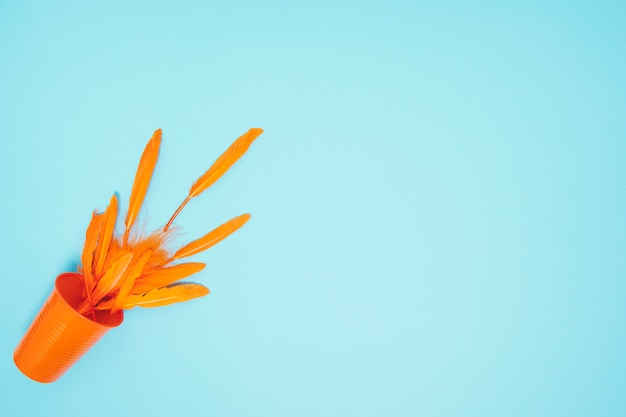 Orange federn, die das plastikglas auf blauem hintergrund überlaufen