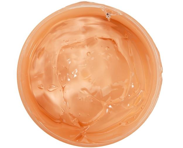 Orange feuchtigkeitsspendende durchscheinende creme in einem plastikglas, draufsicht