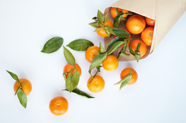 Orange frische mandarinen mit grünen blättern in einer papiertüte