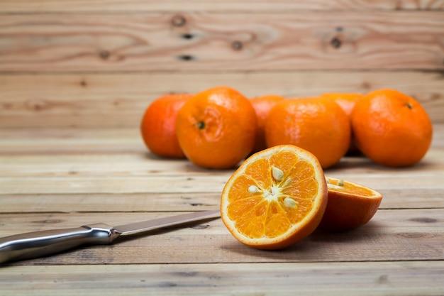 Orange frucht auf holztisch mit messer