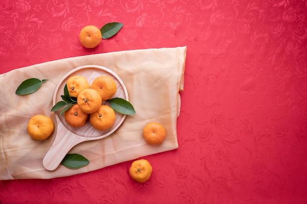Orange frucht mit kopienraum auf rotem beschaffenheitshintergrund