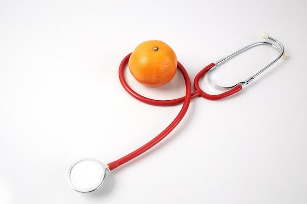 Orange frucht mit rotem stethoskop auf weiß