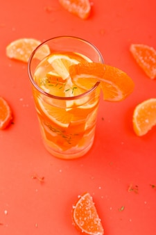 Orange fruchtcocktail, detoxwasser auf orange oberfläche