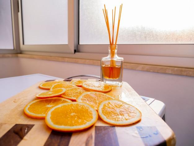 Orange fruchtscheibe mit aromatischem lufterfrischer des schilfs auf hölzernem schneidebrett.