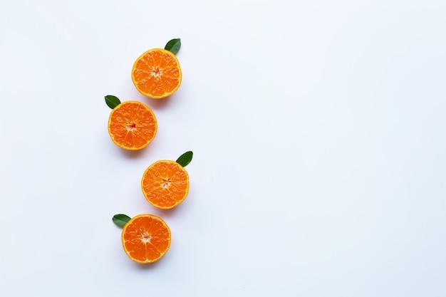 Orange früchte und grünblätter auf einem weißen hintergrund.