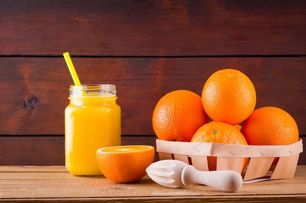 Orange früchte und saft auf hölzernen brettern. zitrusfrüchte zur saftherstellung mit handentsafter. orangen in holzkiste. einmachglas mit orangensaft