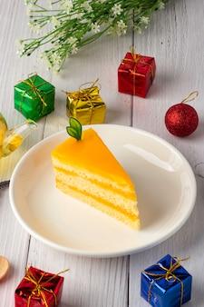 Orange fudge kuchen auf einem weißen teller, dreieckiger kuchen, schöne dekoration mit geschenkboxen und blumen