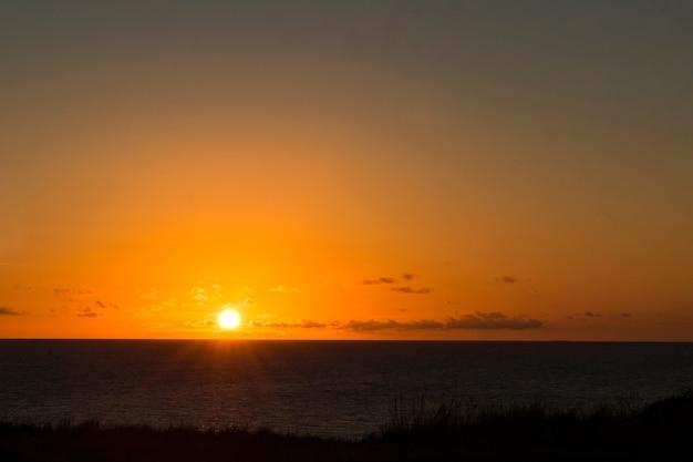 Orange-gelbe farben des sonnenuntergangshimmels unter meer schöner himmel auf seemeer im vordergrund gelbe sonne