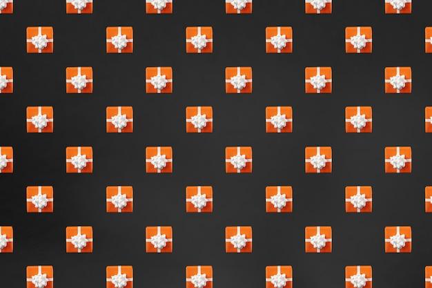 Orange geschenkbox auf schwarzem hintergrund. halloween-konzept. kreatives design, minimales flaches lay-konzept. muster.