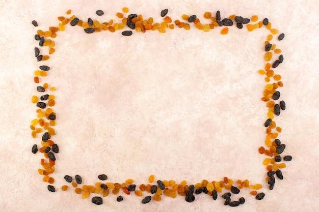 Orange getrocknete rosinen von oben mit schwarzen getrockneten früchten, die quadrat auf rosa formen
