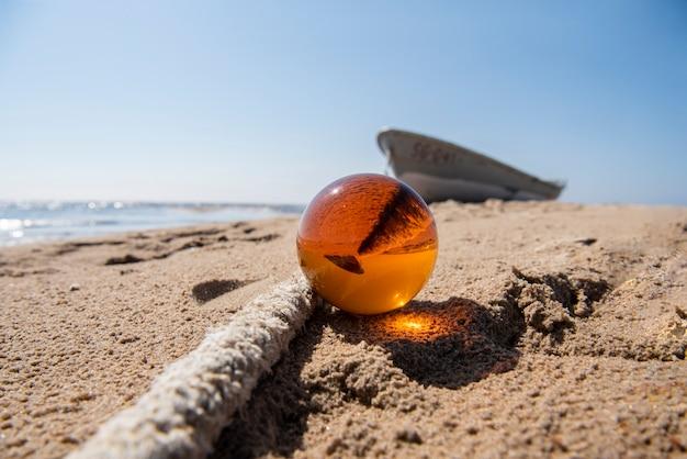 Orange glaskugel auf sand nahe dem meer